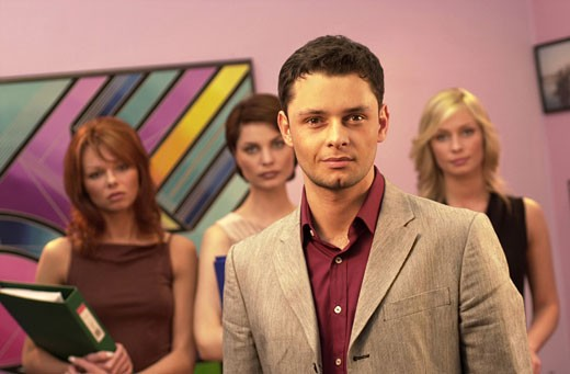 Stock Photo: 1598R-217754 Portrait of a businessman with three businesswomen standing behind him in an office