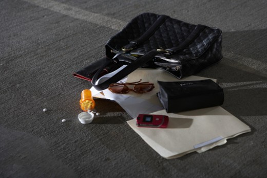 Purse and scattered items on ground in parking garage, elevated view : Stock Photo