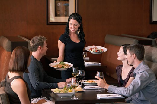 Waitress bringing food to four adults at table in restaurant : Stock Photo