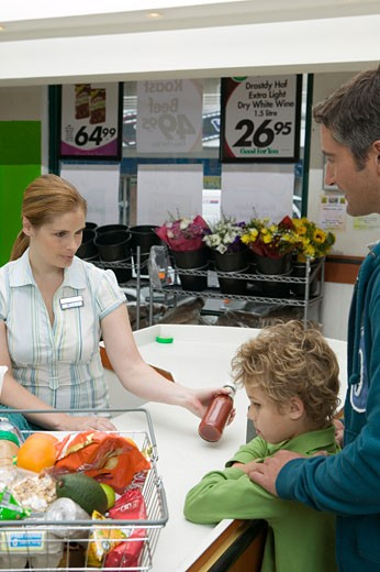 Father and son (6-8) at supermarket checkout : Stock Photo