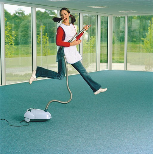 Woman wearing apron indoors, holding vacum cleaner, jumping in air : Stock Photo