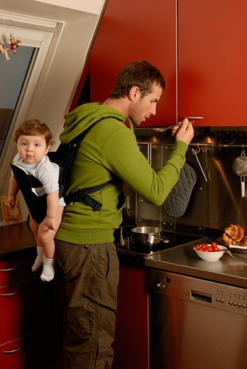 Stock Photo: 1598R-223626 Father carrying baby son (7-9 months) on back while cooking in kitchen