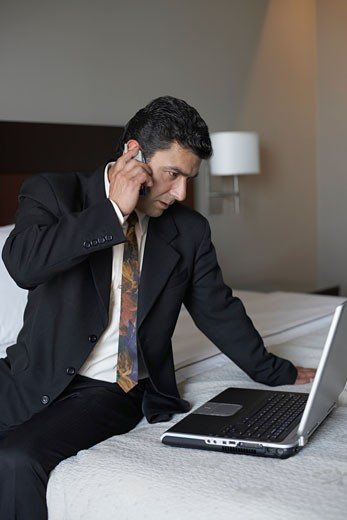 Businessman using a mobile phone and a laptop on the bed : Stock Photo