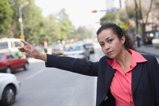 Stock Photo: 1598R-224196 Businesswoman raising her arm to hail a taxi