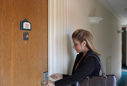 Stock Photo: 1598R-224603 Side profile of a young woman entering a keycard into a hotel room door