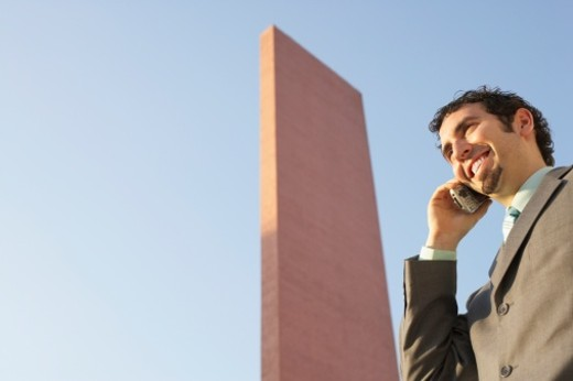 Low angle view of a businessman talking on a mobile phone : Stock Photo