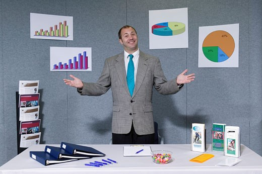 Man standing at trade show booth, charts and graphs on wall behind : Stock Photo