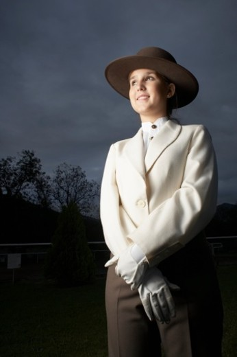 Low angle view of a young woman wearing horse riding gear : Stock Photo