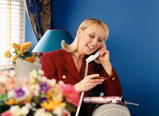 Stock Photo: 1598R-225011 Woman using telephone, holding credit card