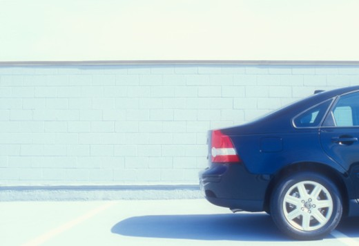 Rear section of car by wall, side view : Stock Photo