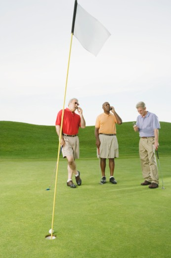 Three golfers all using mobile phones on golf course : Stock Photo