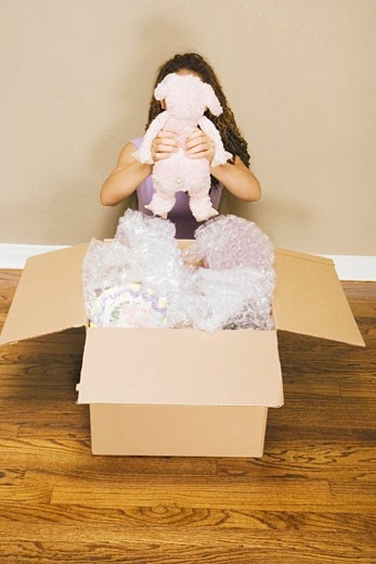 Young woman unpacking stuffed animal from box : Stock Photo
