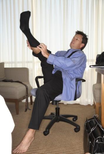 Man putting on socks in hotel room : Stock Photo