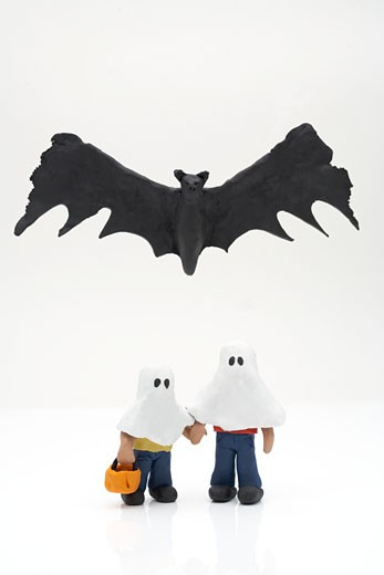 Clay bat above two child figurines in ghost costumes against white background : Stock Photo