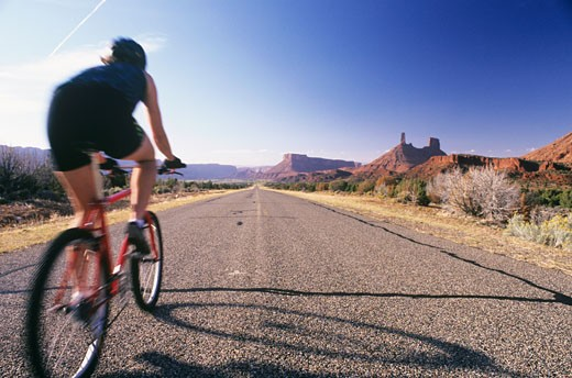 USA, Utah, Castle Valley State Park, Female mountain biker on road, rear view : Stock Photo