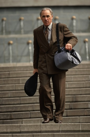 Businessman Walking with a Tennis Racket : Stock Photo