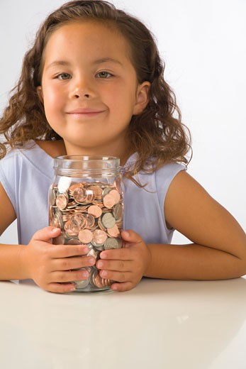 Stock Photo: 1598R-2287 Girl (5-7) holding jar filled with coins, smiling, portrait