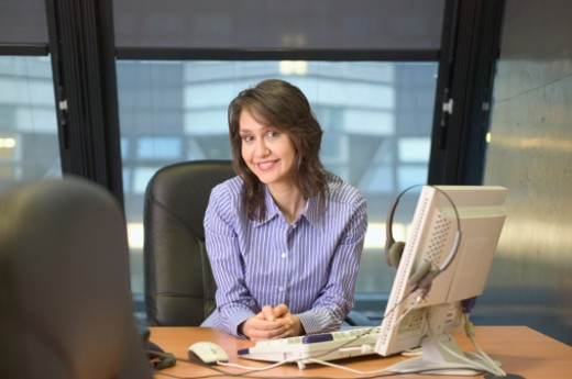 Businesswoman at desk with computer, smiling, portrait : Stock Photo