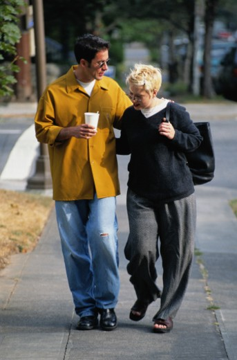 Couple Walking Down a Sidewalk : Stock Photo