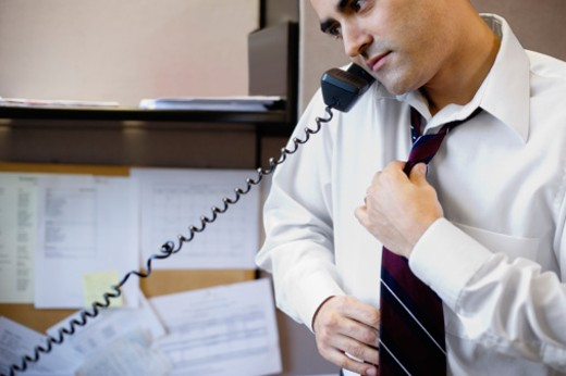 Businessman on telephone adjusting tie : Stock Photo
