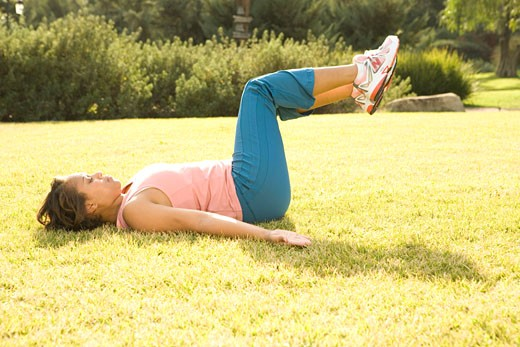 Young woman lying on back in garden, doing exercises, side view : Stock Photo