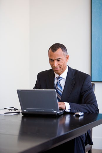 Mature businessman sitting typing on laptop computer : Stock Photo
