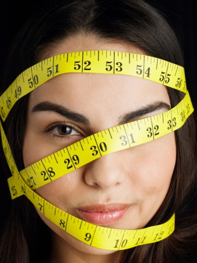 Young woman with tape measure wrapped around head, close-up : Stock Photo