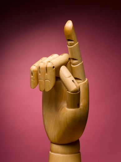 Wooden hand with index finger extended, close-up : Stock Photo