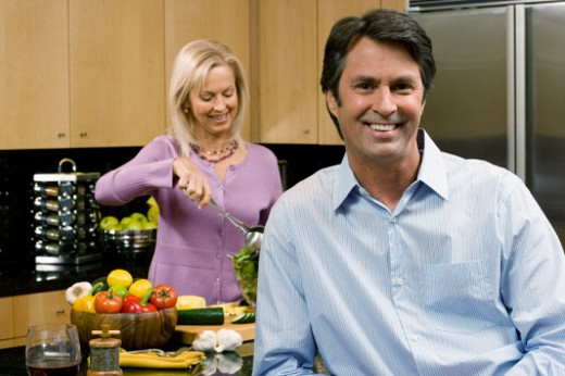 Woman in kitchen preparing salad, man smiling in foreground : Stock Photo