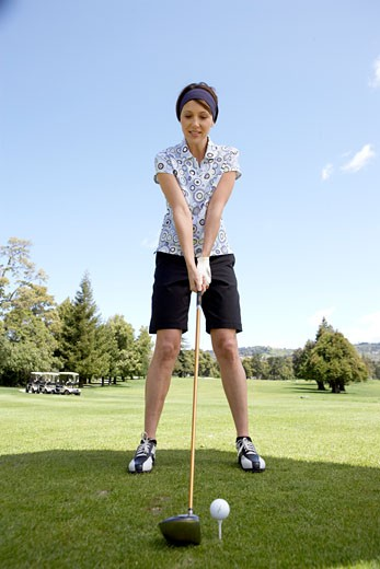 Stock Photo: 1598R-235786 Female golfer holding club near golf ball