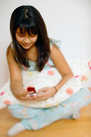 Stock Photo: 1598R-235998 Girl (12-13) sitting on hardwood floor, using mobile phone