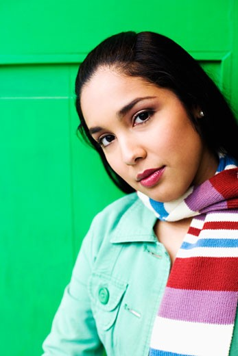 Young woman leaning against green door, portrait : Stock Photo
