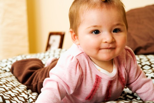 Baby (6-9 months) smirking, close-up : Stock Photo