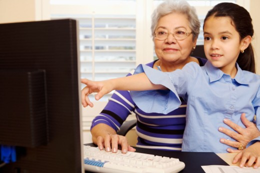 Girl (8-9) pointing at computer screen with grandmother : Stock Photo