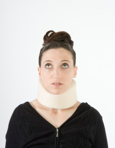Woman wearing neck brace, looking up : Stock Photo