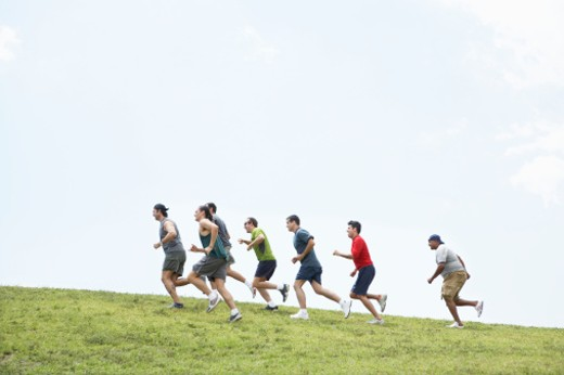 Group of men running up hill, side view : Stock Photo