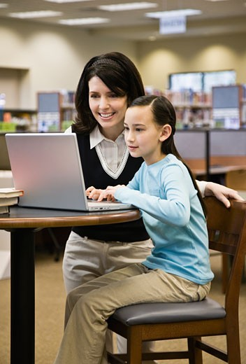 Stock Photo: 1598R-237279 Mother and daughter (8-9) using laptop in library
