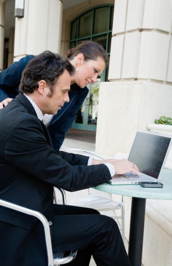 Businessman and businesswoman working on laptop at outside cafe table : Stock Photo