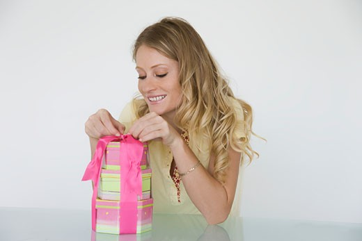 Young woman sitting at table opening present : Stock Photo