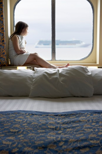 Girl (6-7) sitting at cabin window on cruise ship : Stock Photo