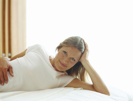 Stock Photo: 1598R-23853 Mature woman lying with head in hand, smiling, portrait
