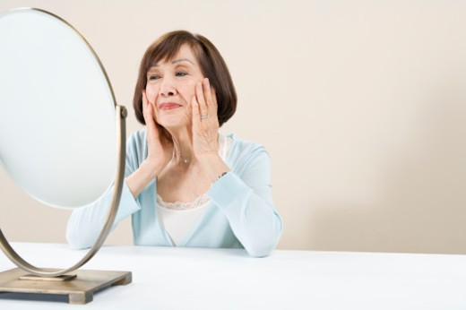 Stock Photo: 1598R-239073 Woman sitting at table looking in mirror