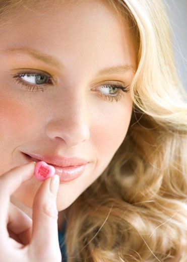 Young woman holding candy to mouth, looking away, close-up : Stock Photo