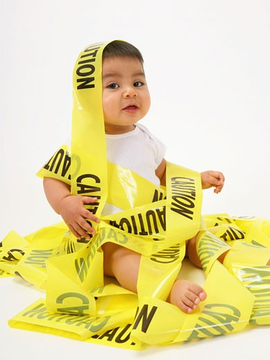 Stock Photo: 1598R-239978 Baby boy (15-18 months) sitting on floor wrapped in 'caution' tape
