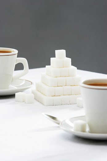 Two coffee cups and sugar cubes pyramid on table : Stock Photo