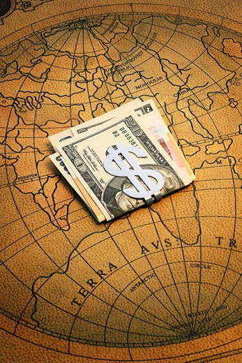 Stock Photo: 1598R-240376 American dollar bills with dollar sign clip on world map