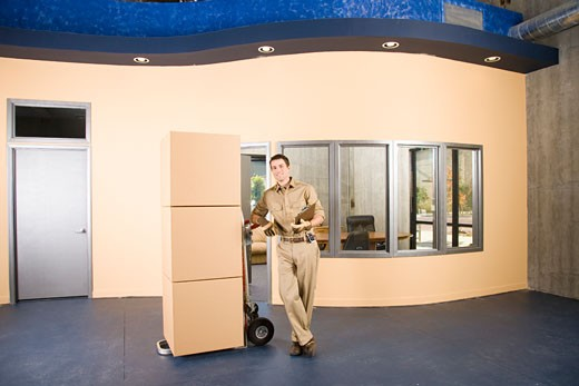 Delivery man with boxes in warehouse, portrait : Stock Photo
