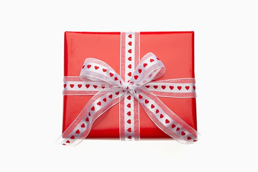 Gift decorated with red paper and ribbon with heart symbols : Stock Photo