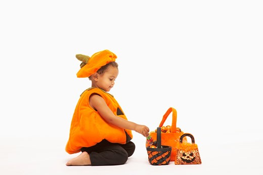 Boy (2-3) wearing Halloween costume with candy baskets, studio shot : Stock Photo