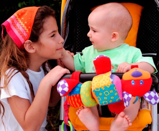 Stock Photo: 1598R-241387 Young girl kneeling besides a baby, sitting in a pram